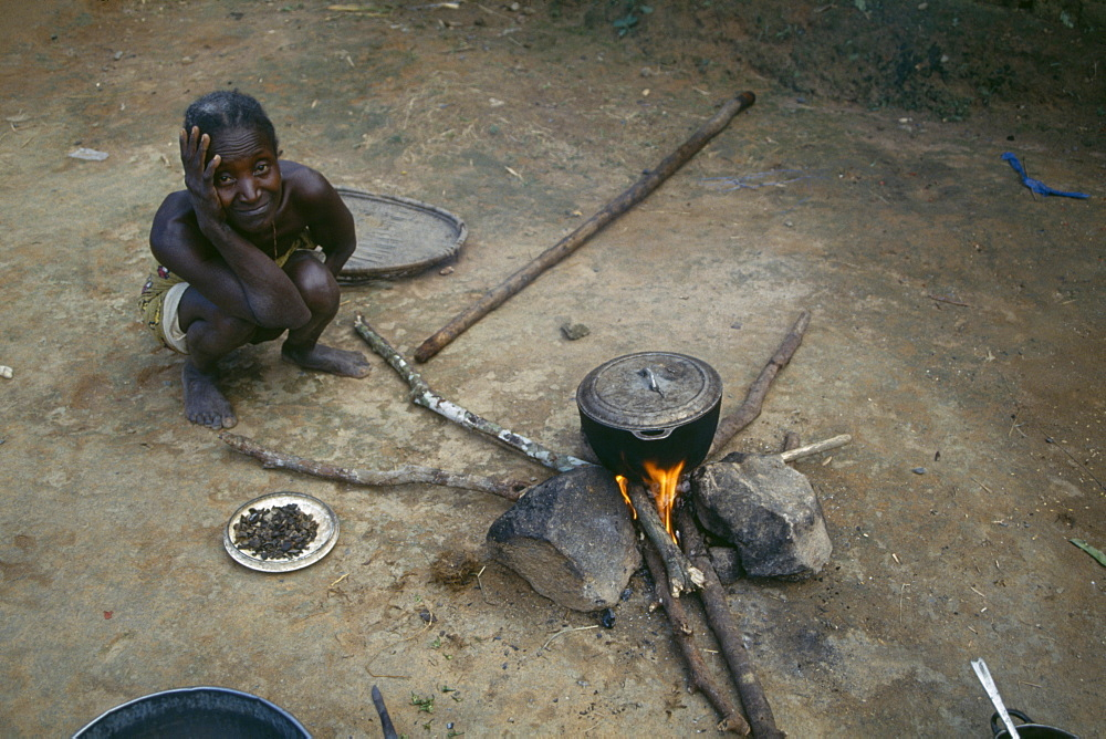 LIBERIA  People Woman cooking on open fire with cooking pot balanced on stones.