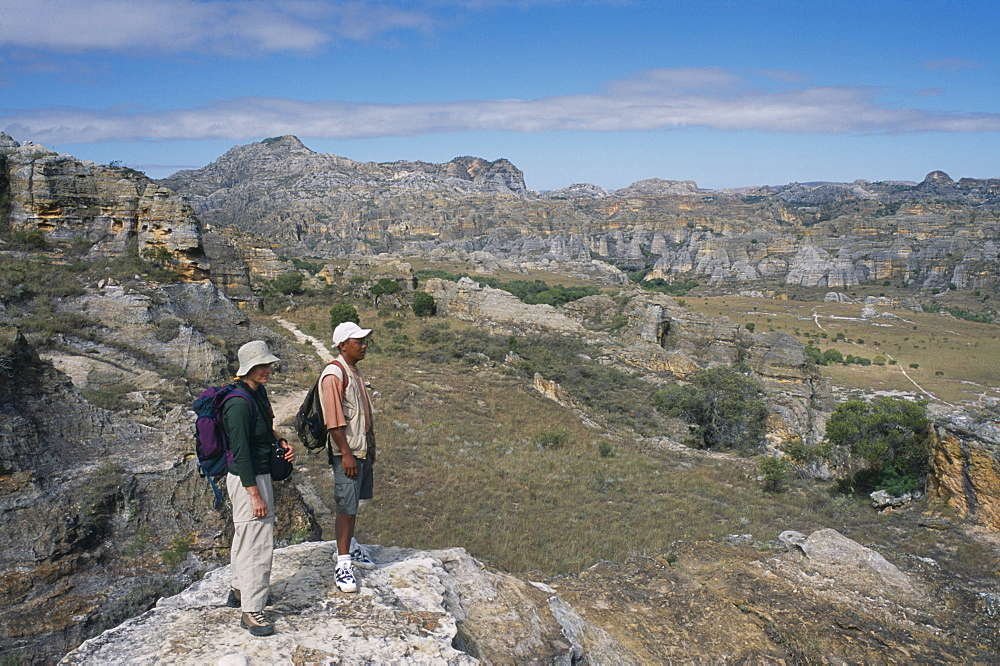 MADAGASCAR  Isalo National Park Tourist and guide standing on edge of rock looking over craggy sandstone massifs