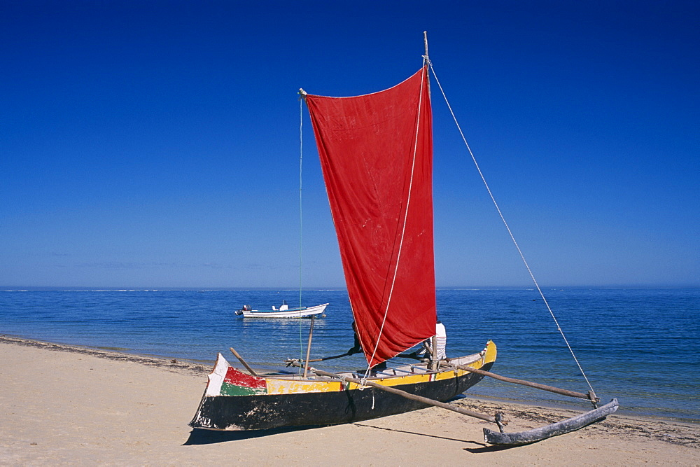 MADAGASCAR  Tulear Ifaty Beach. Pirogue boat with red sail on sandy beach next to the waters edge