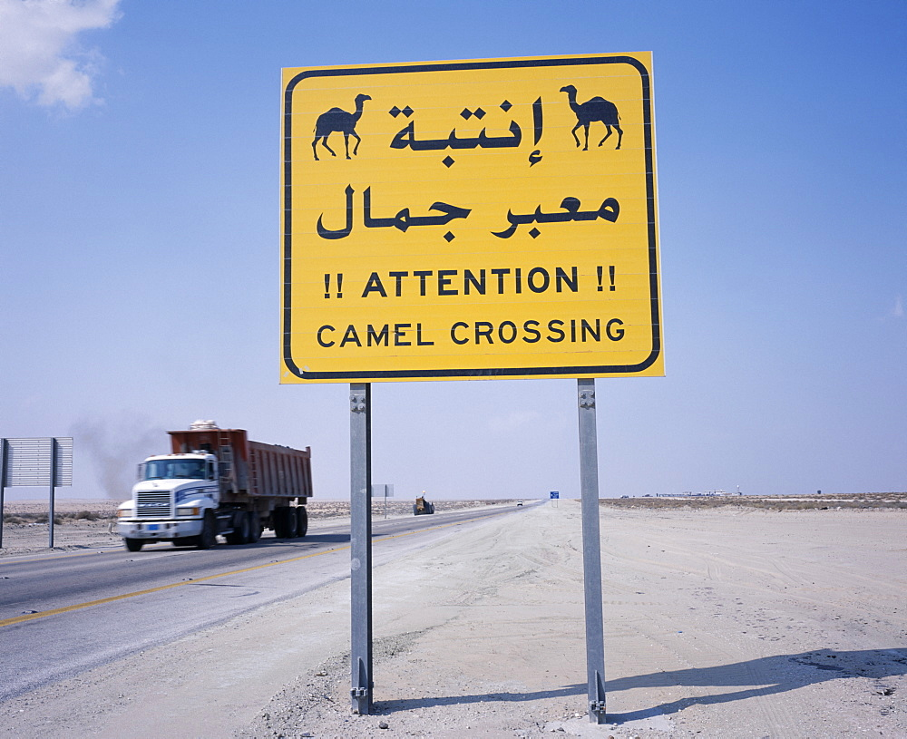 SAUDI ARABIA  Transport Camel Crossing road sign on Eastern Highway to Dammam with passing truck behind. Lorry