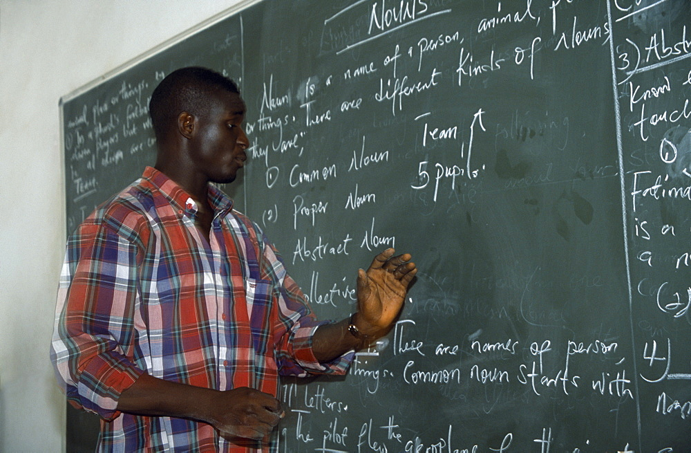 NIGERIA  Kano English teacher standing beside blackboard giving grammar lesson. African Learning Lessons Nigerian Teaching Western Africa
