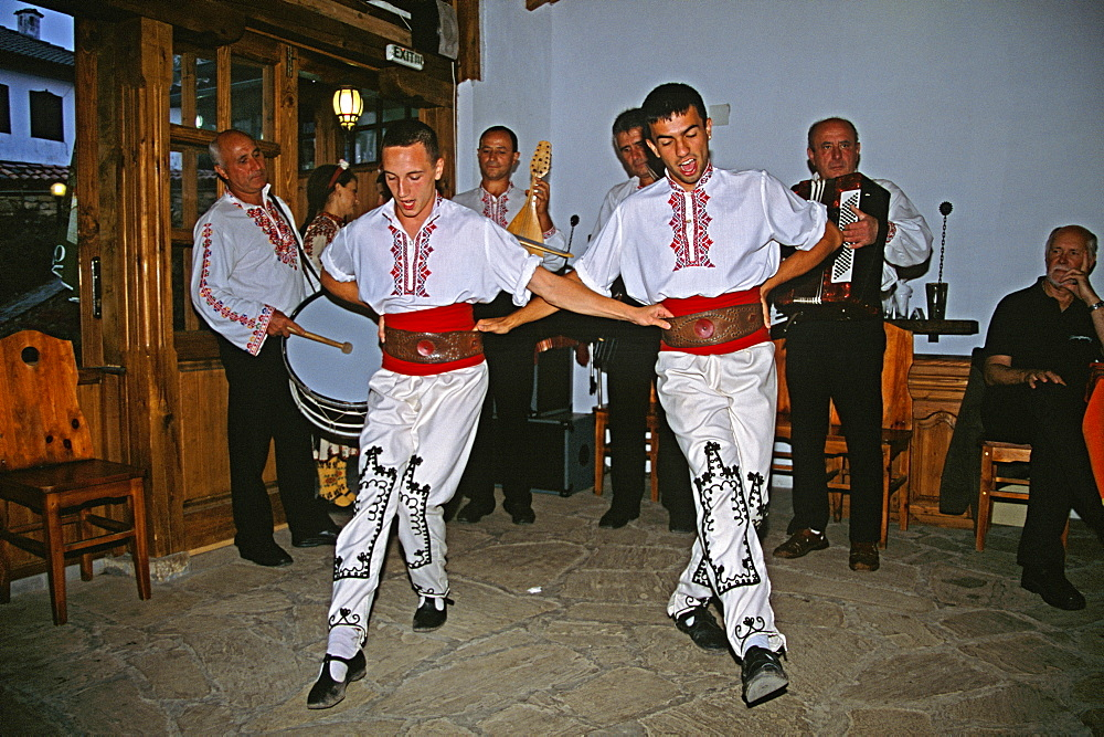 BULGARIA  Arbanassi Male dancers in national costume dancing. Travel Tourism Holiday Vacation Explore Recreation Leisure Sightseeing Tourist Attraction Tour Arbanassi Bulgaria Bulgarian East Eastern Europe European Entertain Entertainer Entertainment Entertaining Folklore Smiling Smile Happy Happiness National Costume Calendar Festival Festive Tradition Traditional Culture Cultural Ethnic Folk Group Man Men Male Gentleman Vivid Vibrant Country Dress Community Village Local Floor Show Dance Dancing Dancer Dancers Restaurant Embroidery Embroidered Sewing Sewn Sew Clothes Clothing Garments Garment Adorn Adornment Smart Fashion Fashionable Wear Wearing Worn Detail Detailed Extrovert Activity Active Pattern Patterned Drum Drummer Music Musical Musician Band Contented Eastern Europe