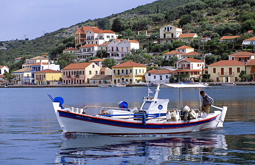 GREECE Ionian Islands Ithaca Vathi. Boat moving in harbour and Vathi town behind.  Travel Tourism Holiday Vacation Explore Recreation Leisure Sightseeing Tourist Attraction Tour Destination Vathi Ithaca Ithaka Ithica Ithika Ithaki Ithaci Greece Grecian Greek Ionian Sea Waterfront Waterside Water Calm Still Quiet Peaceful Picturesque Unspoiled Tranquility Tranquil Harbour Harbor Harbourside Harborside Hill Hillside Backdrop Vivid Vibrant Town Tradition Traditional Culture Cultural Community Buildings Houses Homes Residence Abode Dwellings Real Estate Property Apartments Fishing Boat Reflection Reflect Steep Man Gentleman Male Person Adult Fisherman Ethnic Business Work Working Worker Workplace Career Job Enterprise Enterprising Livelihood Occupation Moving Travelling Transport Transportation Foreground Interest Vacation Classic Classical Ellada Historical Male Men Guy Older Reflexion Southern Europe Traveling European History Male Man Guy