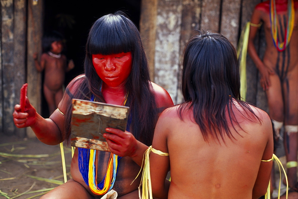 BRAZIL Mato Grosso Indigenous Park of the Xingu Young Panara women applying red karajuru face and body paint in preparation for dance.   Formally known as Kreen-Akrore  Krenhakarore  Krenakore  Krenakarore  Amazon American Brasil Brazilian Female Woman Girl Lady Indegent Kreen Akore Latin America Latino South America Female Women Girl Lady Immature