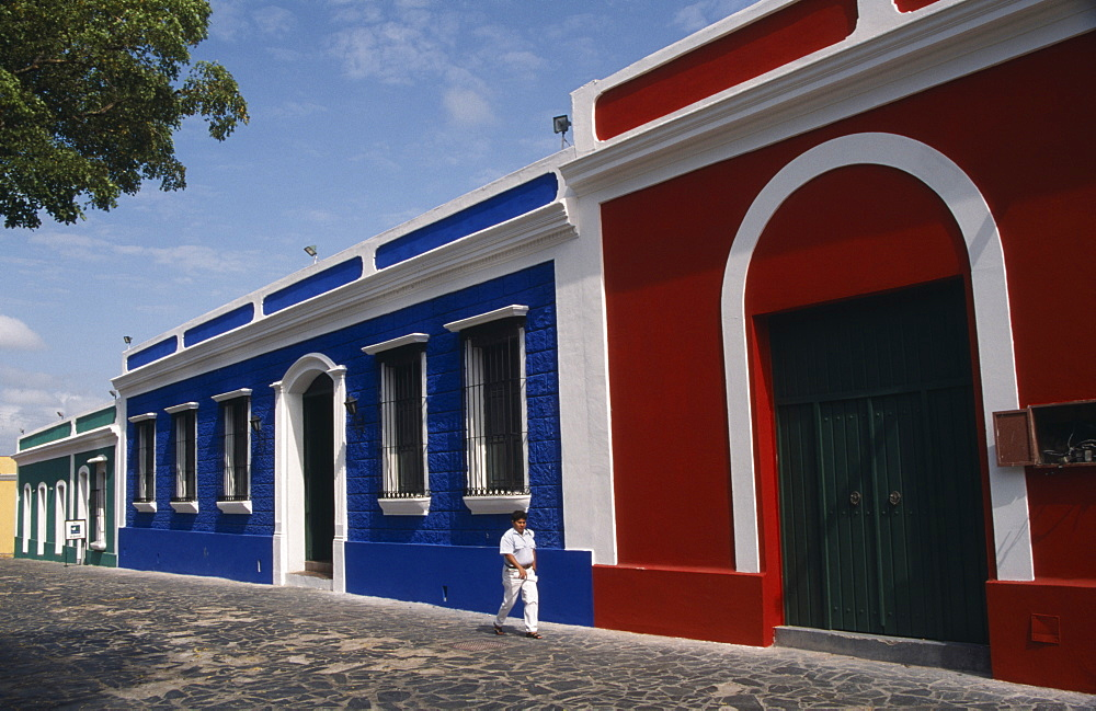 VENEZUELA  Bolivar State Ciudad Red  blue and white painted house frontages near Plaza Bolivar with a person walking past