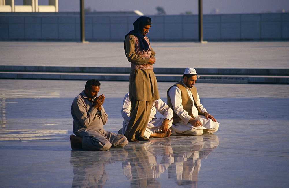 Faisal Mosque, Four men at prayer reflected in surface of shiny marble floor, Islamabad, Pakistan