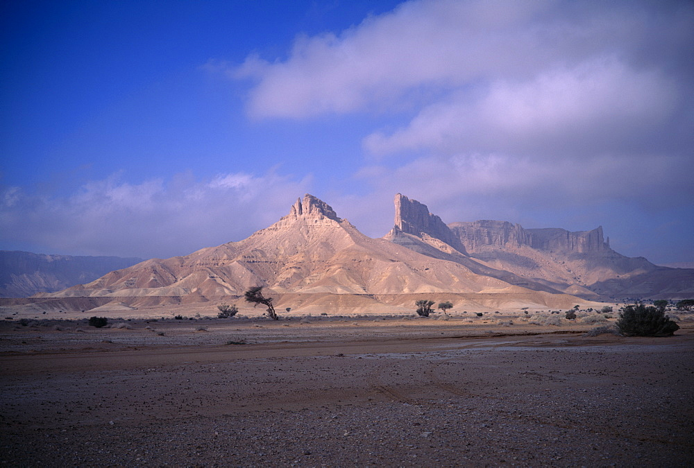 Desert landscape with triangular rock formation and pinnacles in sunlight, Howtah, Saudi Arabia