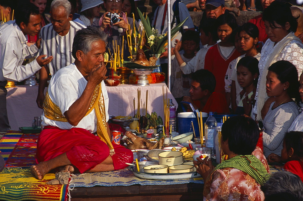 Shaman at ceremony smelling the offerings of food brought by the Khmer people, Angkor Wat, Siem Reap Province, Cambodia