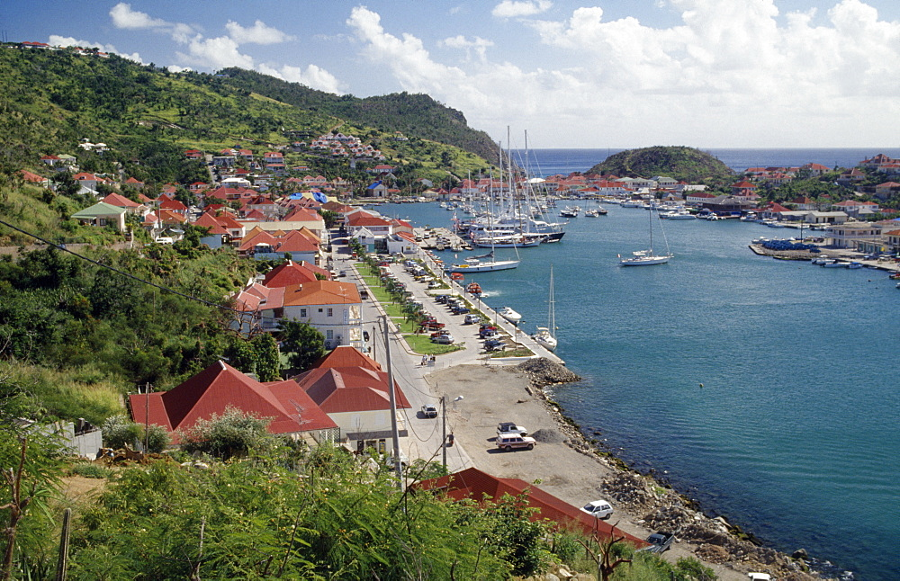 View over the port with yachts on water and houses built along bottom of hillside, Gustavia, St Barthelemy