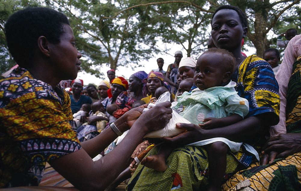 Health worker giving nutritional advice to mothers with vulnerable babies during food distribution at Orukinga refugee camp near the Rwandan border, Medical, Uganda