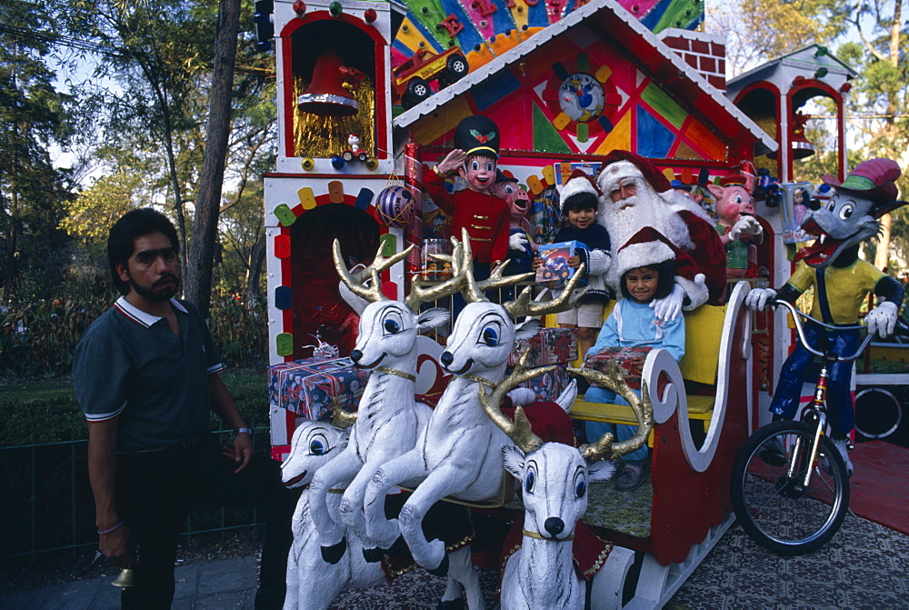 Children visiting Father Christmas in his sleigh in Mexico City Park, Mexico City, Mexico