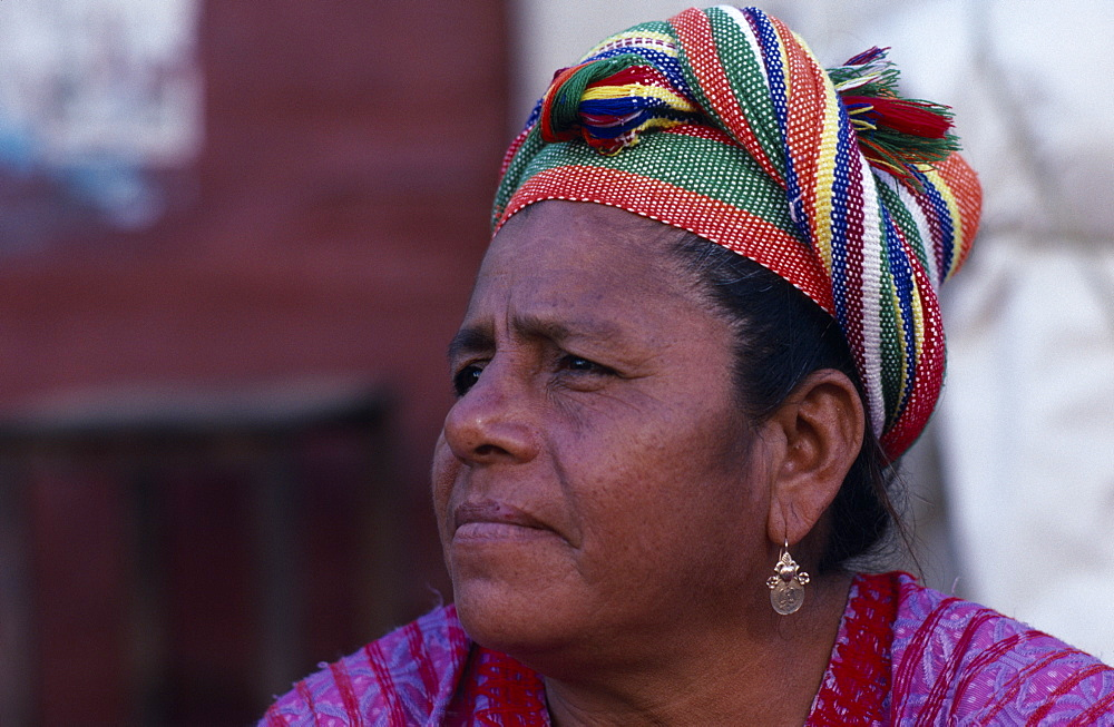 Head and shoulders portrait of woman wearing coloured headscarf and gold earring, Three quarters profile left, Juchitan, Oaxaca, Mexico