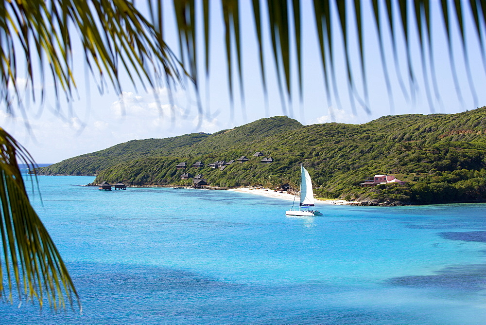 Raffles Resort Hotel with a catamaran leaving Carenage Bay passing the pink Villa Juliet and the Amrita Spa on Godahl Beach, Canouan, St Vincent & The Grenadines