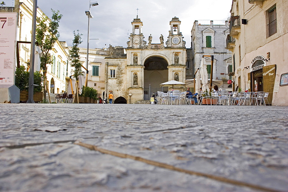 Main square in ancient city of Sassi di Matera or the Stones of Matera originating from a prehistoric cave settlement, UNESCO World Heritage Site, Cafe bar with outside seating overlooked by church and bell tower, Matera, Basilicata, Italy