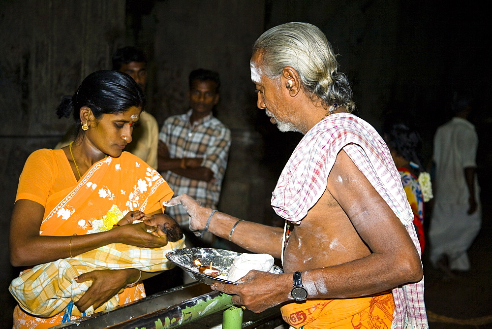 Brahmin blessing a baby, held in his mothers arms, Meenakshi Temple, Madurai, Tamil Nadu, India,