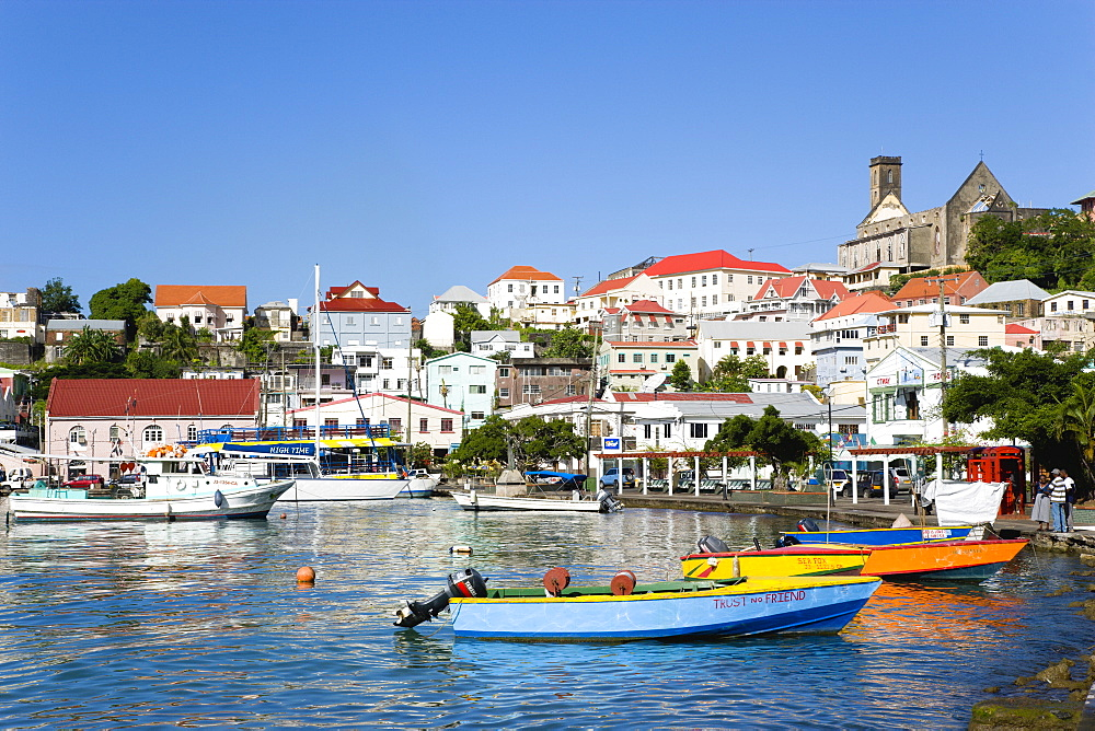 Water taxi boats moored in the Carenage harbour of the capital city of St. Georges, with the roofless cathedral damaged in Hurricane Ivan on skyline, Grenada, West Indies, Caribbean, Central America