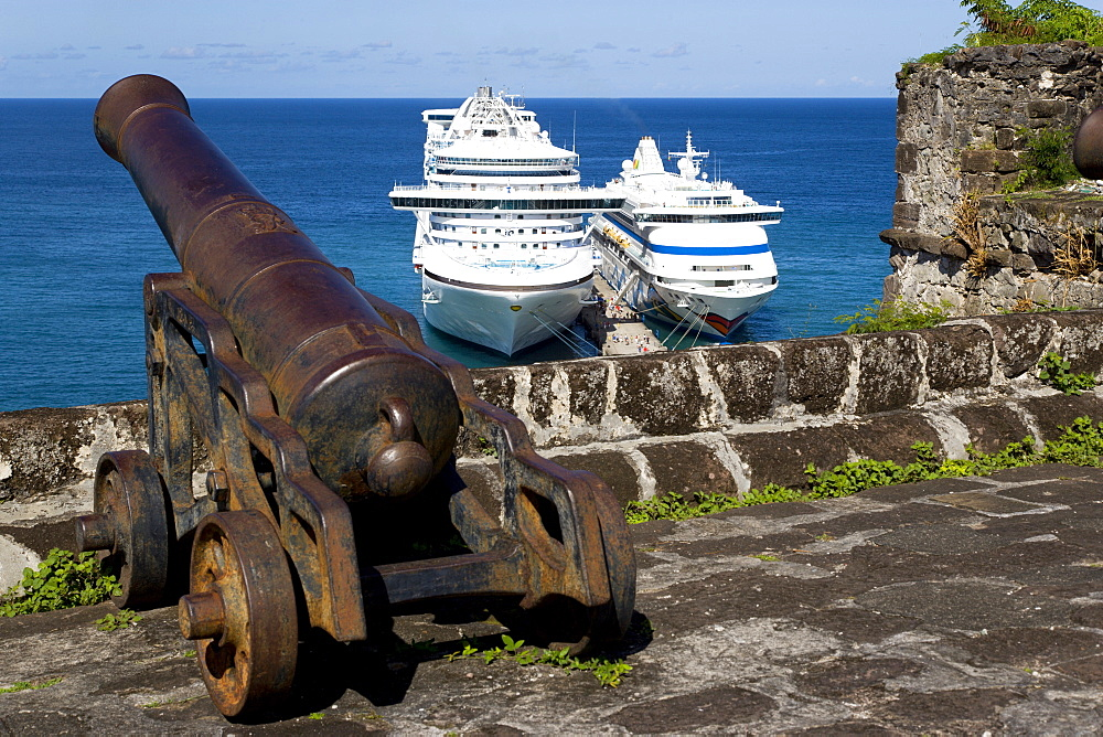 An old cannon pointing out to sea at Fort George with the Caribbean Princess and Aida Aura cruise ships moored below at the cruise ship terminal, St. Georges, Grenada, West Indies, Caribbean, Central America