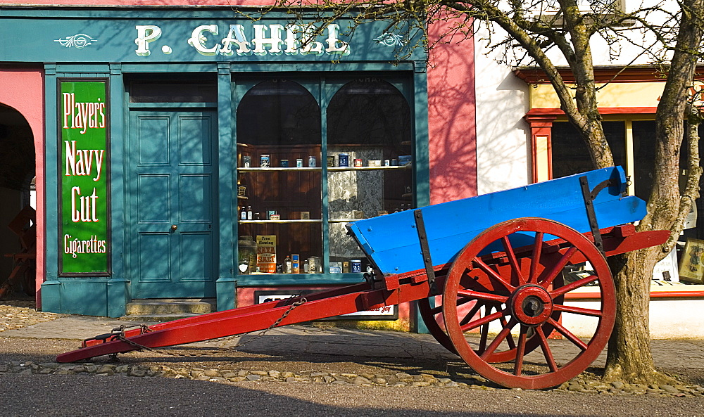 The Village Street denotes village life in 19th century Ireland  Blue and Red wooden cart outside P Cahill shopfront.