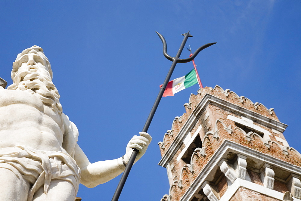 Italy, Veneto, Venice, Centro Storico, Arsenale, Part view of crenellated tower flying Italian tricolour flag with statue of Neptune in foreground against clear blue sky of late summer