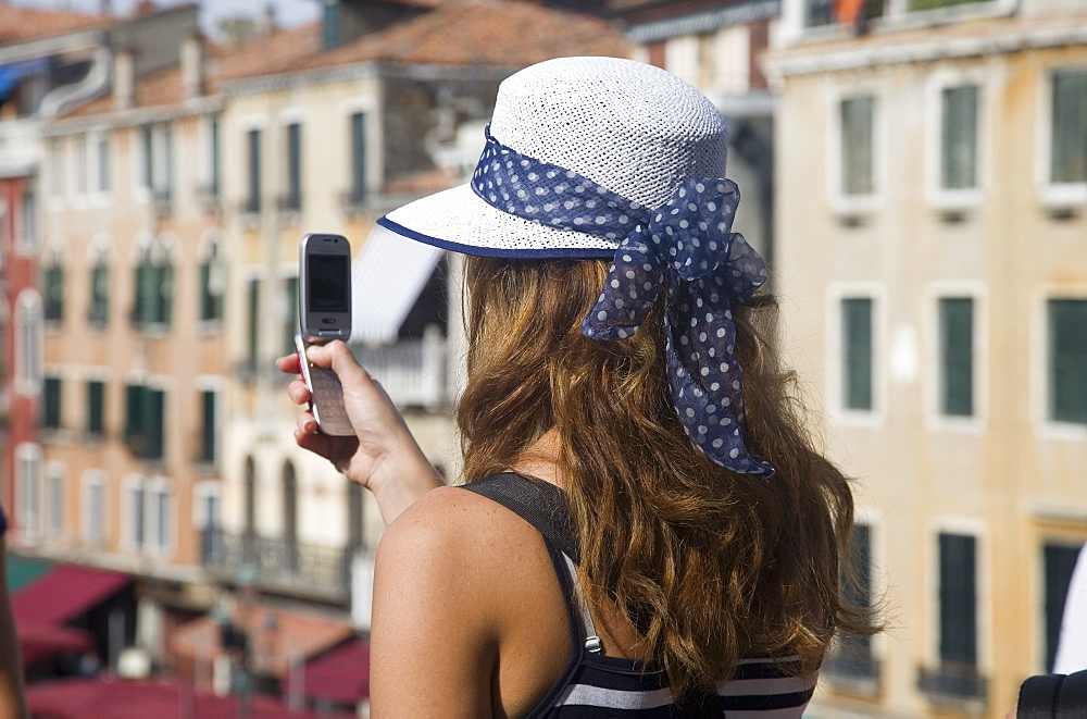 Italy, Veneto, Venice, Young female tourist in white straw hat taking photograph on mobile phone from Rialto bridge looking along Grand Canal