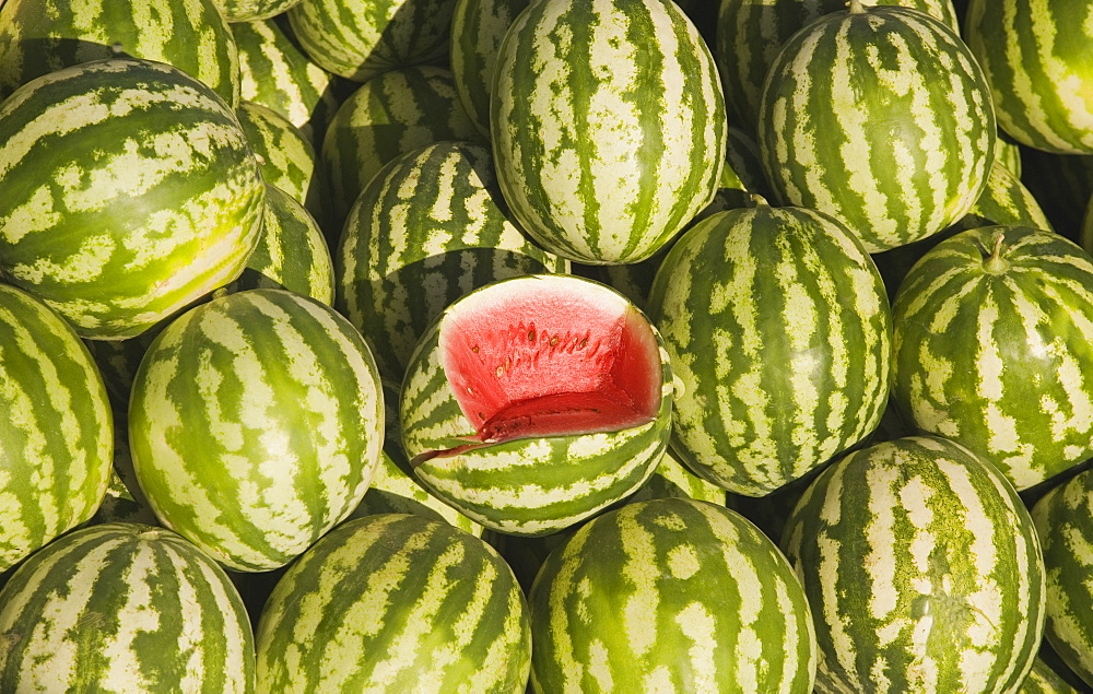 Turkey, Aydin Province, Kusadasi, Fresh watermelon on sale at town produce market with central fruit cut open to show red flesh and seeds