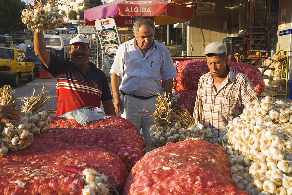 Turkey, Aydin Province, Kusadasi, Stallholder selling garlic at weekly market standing behind stall stacked high with sacks of garlic bulbs and holding up bunch of tied bulbs in late afternoon sunshine