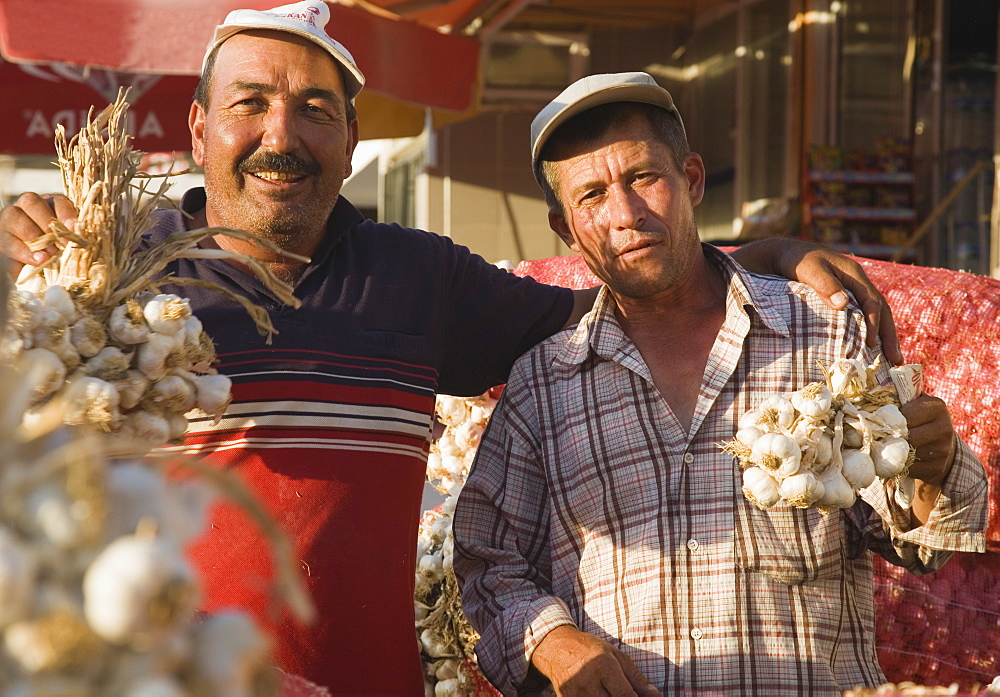 Turkey, Aydin Province, Kusadasi, Stallholders at weekly market with sacks of garlic for sale and holding up bunches of bulbs in late afternoon summer sunshine