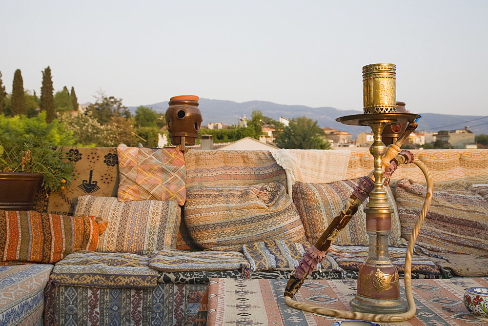 Turkey, Izmir Province, Selcuk, Ephesus, View from rooftop cafe with water pipe on table in foreground and traditional kilim textiles