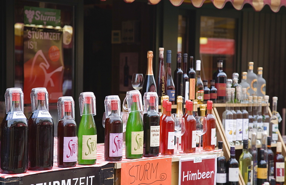 Austria, Vienna, The Naschmarkt, Display of Federweisser, wine in the fermentation stage, known as Sturm in Austria, line of bottles with tasting glasses