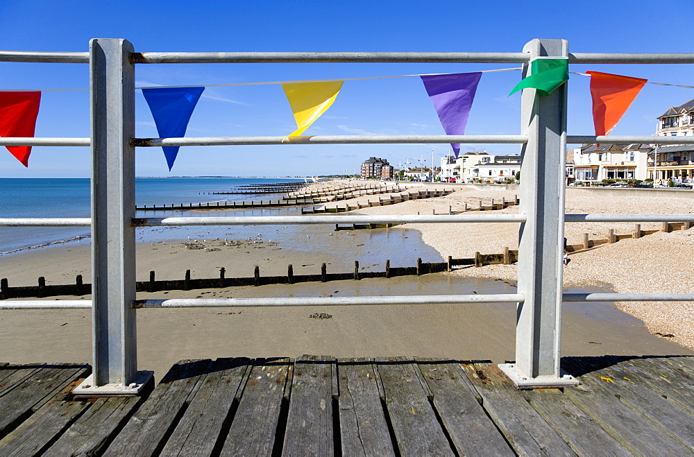 England, West Sussex; Bognor Regis, Wooden groynes at low tide used as sea defences against erosion of the shingle pebble beach seen through metal railings with colourful flags on the pier.