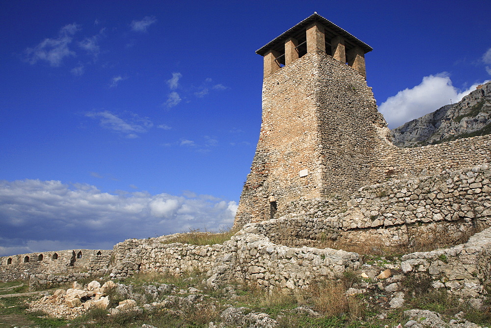 Albania, Kruja. Stone watch tower of Kruja Castle and part ruined walls.