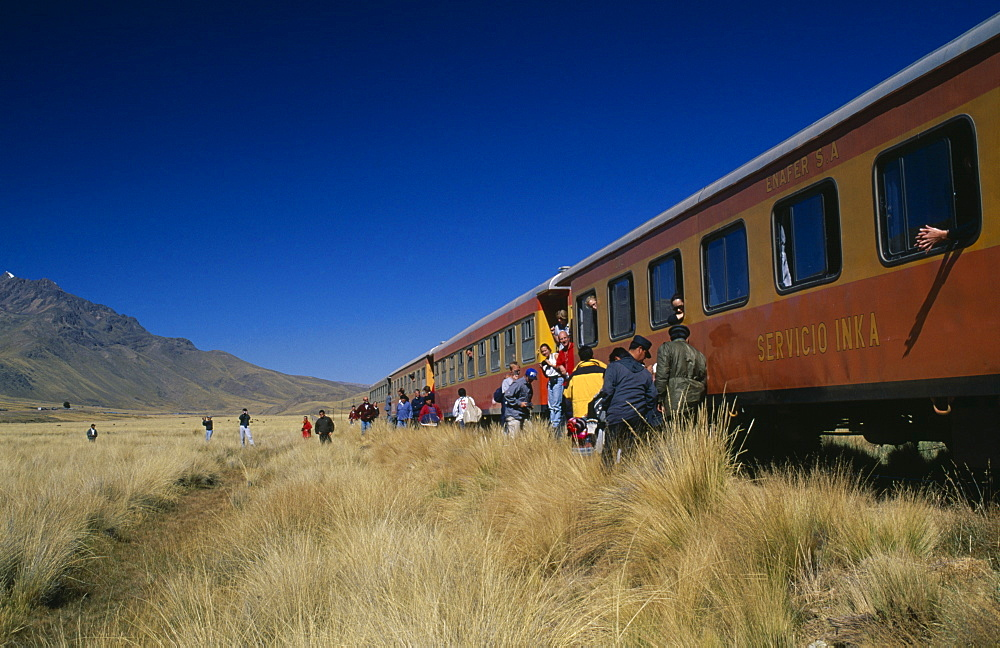 PERU Puno Administrative Department La Raya Train stopped on the altiplano at the highest pass on the line between Puno to Cusco.  People disembarking.