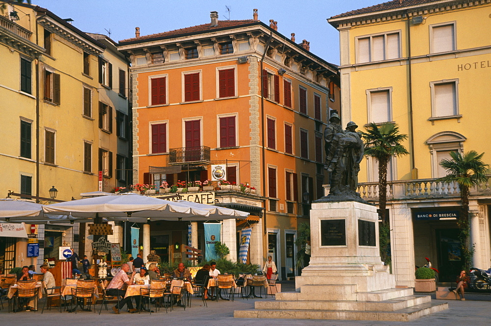 People sitting at outside cafe tables in piazza of town beside Lake Garda Facades of buildings bank and hotel painted pale yellow and orange with window shutters, Salo, Lombardy, Italy