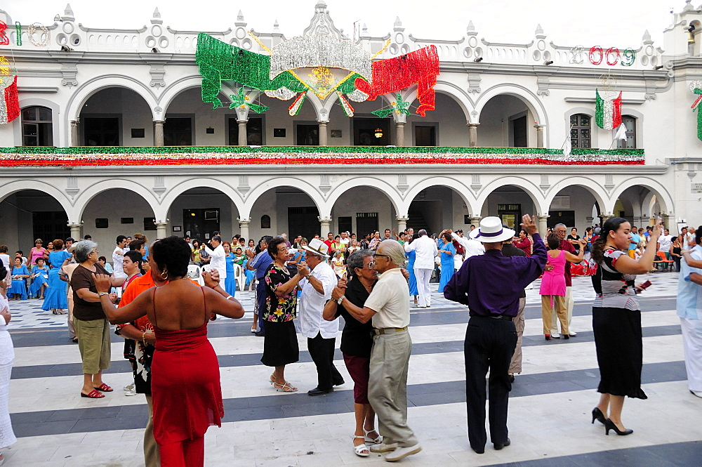 Couples dancing in the Zocalo with facade of government buildings behind hung with bright decorations in the national colours for Independence Day celebrations, Veracruz, Veracruz, Mexico