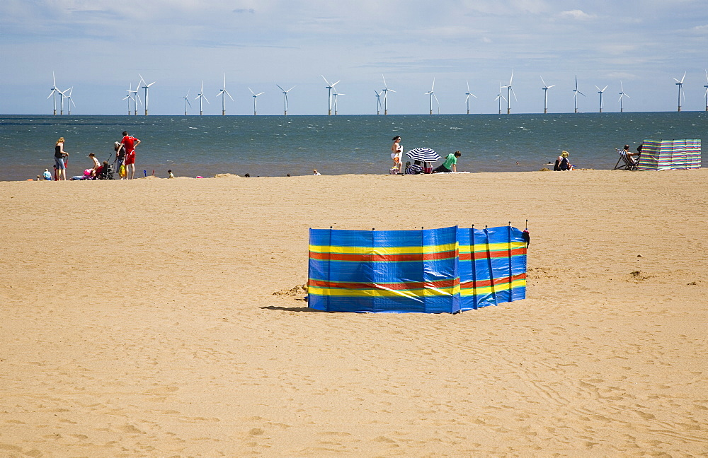 England, Lincolnshire, Skegness, Lincs Wind Farm offshore on the horizon with families and windbreaks on the beach.