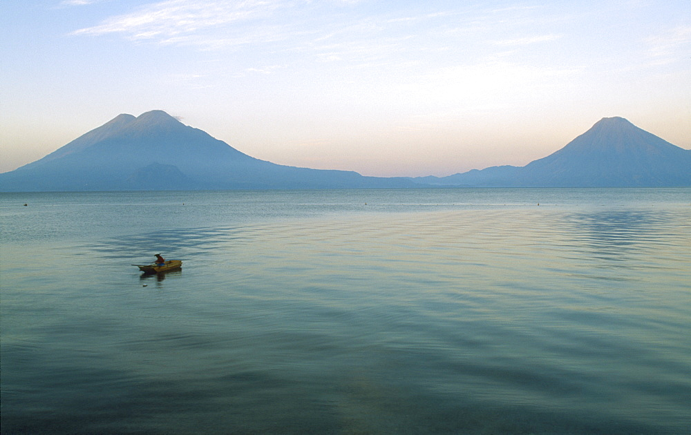 GUATEMALA Panajachel Lake Atitlan View of a boat sailing on the lake with two Volcanoe peaks in the distance.