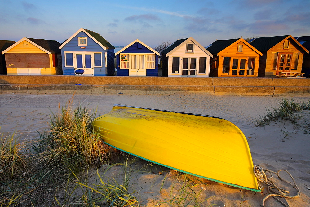 Beach huts and boat on Mudeford Spit, Mudeford, Dorset, England, United Kingdom, Europe