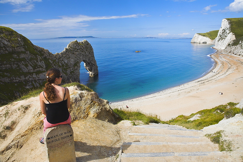 Woman resting on a clifftop sign, looking towards Durdle Door beach, Jurassic Coast, UNESCO World Heritage Site, Dorset, England, United Kingdom, Europe