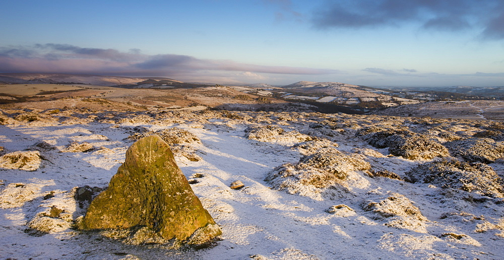 Early morning sunshine lights up the snow covered winter landscape near Haytor Rocks in Dartmoor National Park, Devon, England, United Kingdom, Europe