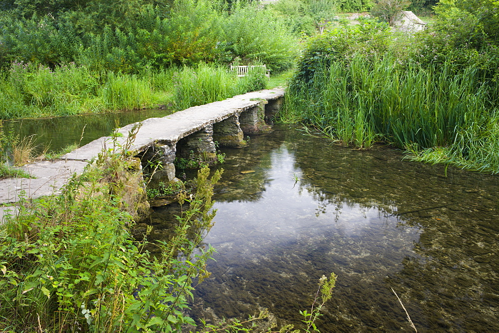 Clapper bridge crossing the River Leach in the pretty Cotswolds village of Eastleach Turville, Gloucestershire, England, United Kingdom, Europe