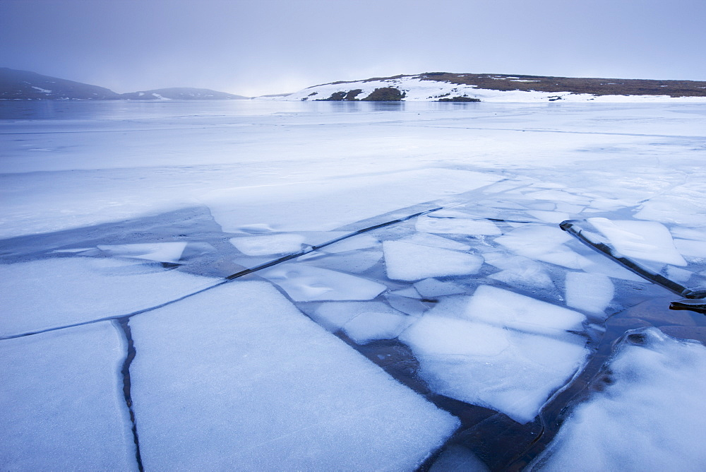 Broken ice on the surface of Llyn y Fan Fawrm, surrounded by hill fog, Black Mountain, Brecon Beacons National Park, Wales, United Kingdom, Europe