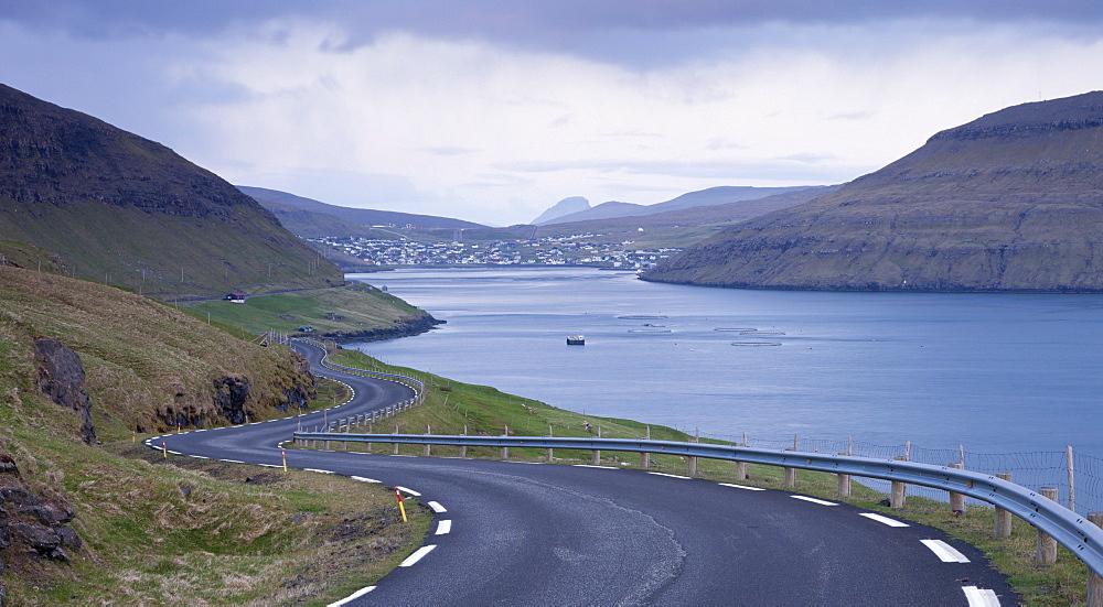 Winding coastal road leading to Sorvagur on the island of Vagar, Faroe Islands, Denmark, Europe