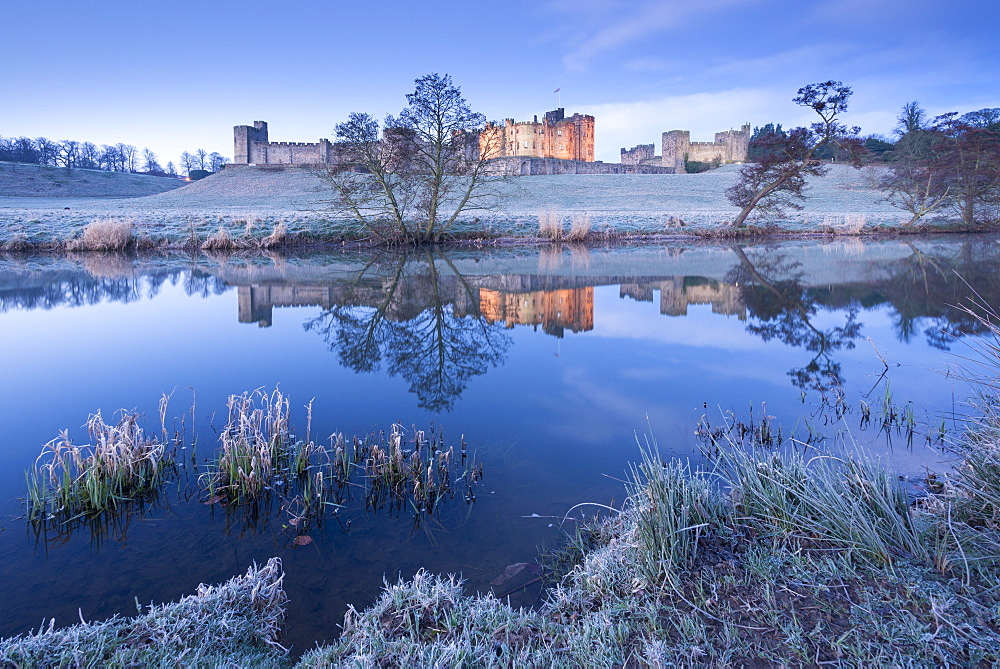 Alnwick Castle reflected in the River Aln on a frosty winter morning, Northumberland, England, United Kingdom, Europe