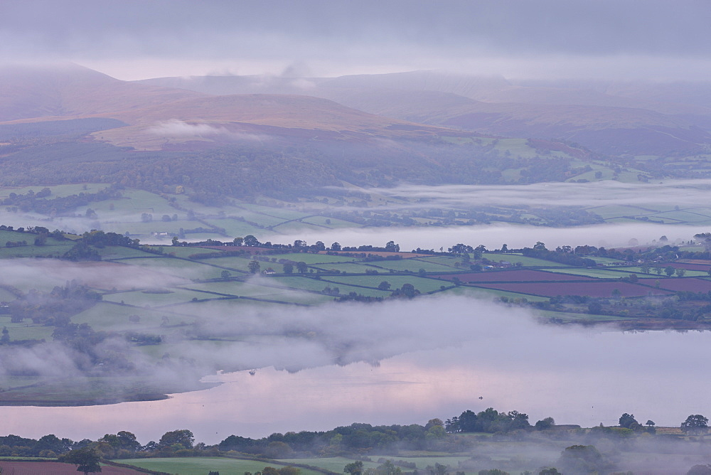 Early morning mist drifts above Llangorse Lake and the rolling fields of the Brecon Beacons National Park, Powys, Wales, United Kingdom, Europe