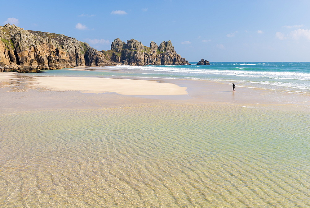 Woman walking alone on Pednvounder Beach at low tide, Porthcurno, Cornwall, England, United Kingdom, Europe