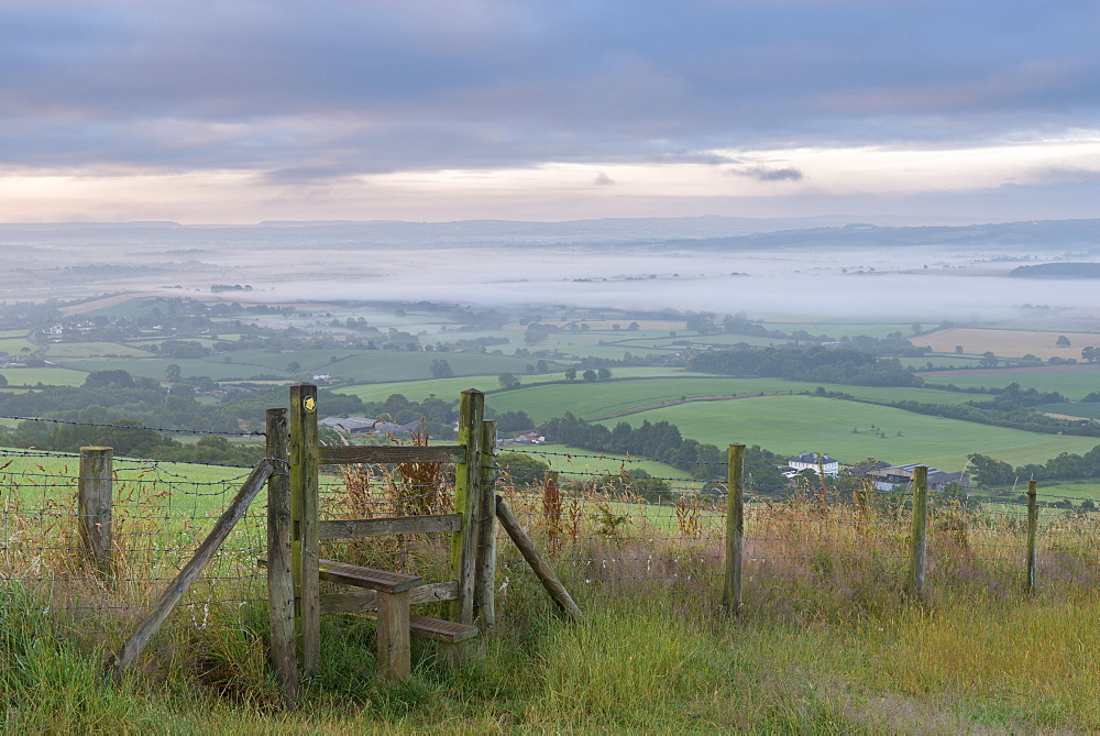 Footpath and stile through farmland with mist covered countryside beyond, Devon, England, United Kingdom, Europe