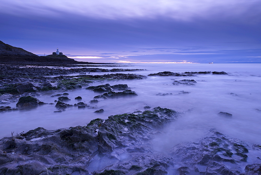Mumbles lighthouse at dawn in winter from Bracelet Bay, Swansea, Wales, United Kingdom, Europe