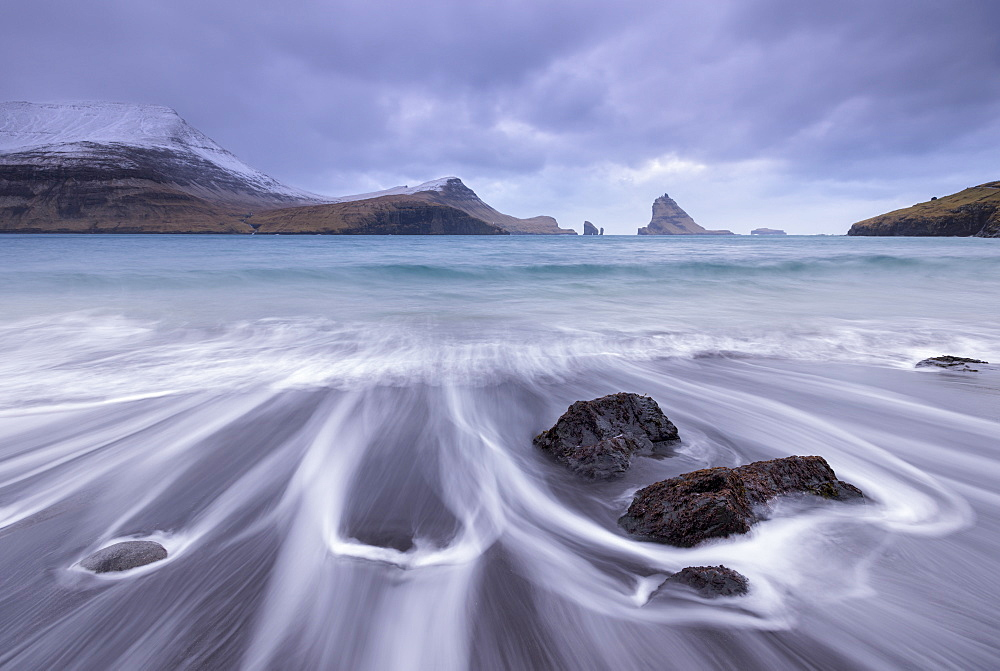 Waves crash onto the black sandy beach at Bour on the island of Vagar in the Faroe Islands, Denmark, Europe