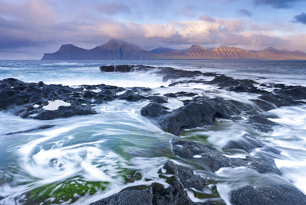 Waves crash against the rocky shores of Gjogv in the Faroe Islands, Denmark, Europe