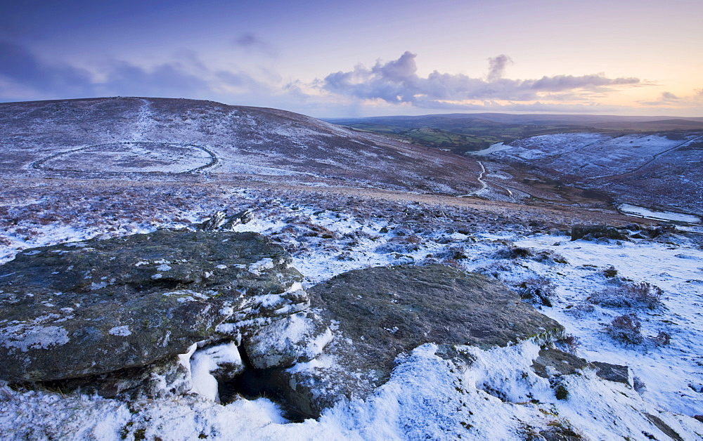 Bronze Age walled settlement of Grimspound, isolated in a snow covered moorland wilderness, viewed from Hookney Tor overlook, Dartmoor National Park, Devon, England, United Kingdom, Europe